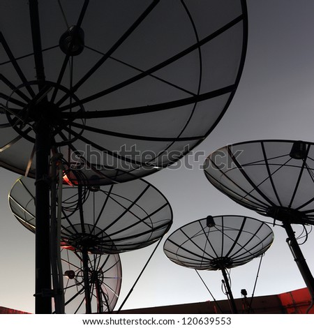 black antenna communication satellite dish over twilight sky in cityscape