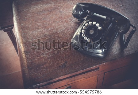 Black antique vintage analog telephone dialing or scrolling phone on wooden table. Contact us concept.