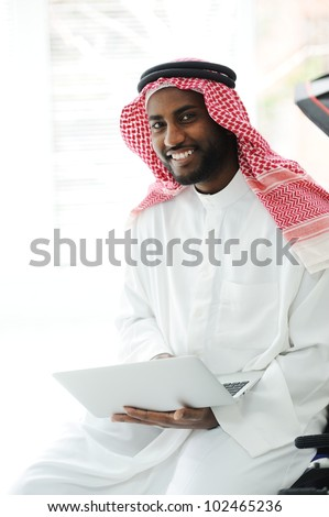 Black Arabic man working on laptop - stock photo