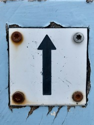black arrow pointing up of forward on small square white metal plate screwed to lightblue wood