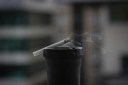 Black ashtray, cigarette and cigarette smoke