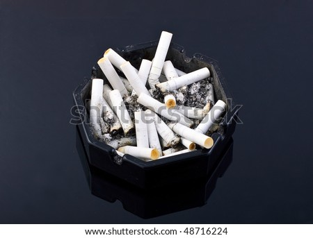 black ashtray with cigarettes on black table