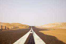 Black asphalt road through the sand dunes of Liwa oasis, United Arab Emirates