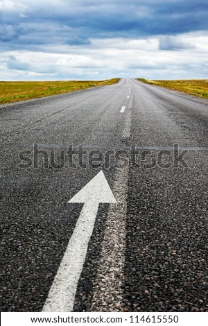 black asphalt road with arrow direction