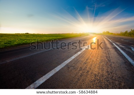 black asphalt road with arrow to sunset