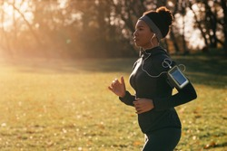 Black athletic woman running while exercising in the park. Copy space.