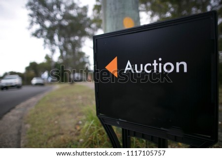 Black auction sign board installed and advertising by estate agency on the public street downtown Sydney city CBD, Australia