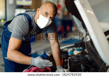 Black auto mechanic wearing protective face mask while examining car engine in auto repair shop.