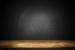Black background of wall and worn old wood table. Empty space for product installation.