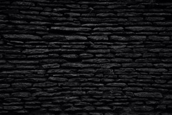 Black background. Old weathered natural sandstone wall. Black and white photo.
