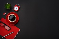 black background red coffee cup note pad alarm clock flower