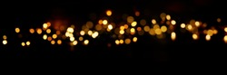 Black background with golden light effects. Horizontal background with blur bokeh effects for christmas time. Special occasion concept with space for text.
