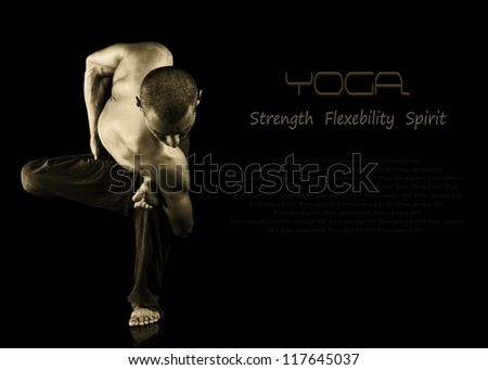 Black background with young man shows difficult yoga exercise - stock photo