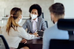 Black bank manager wearing a face mask and using touchpad while having a meeting with a couple in the office.