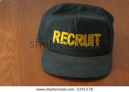 Black Baseball style hat or cap with the word Recruit embroidered in yellow. Official US Military issue.