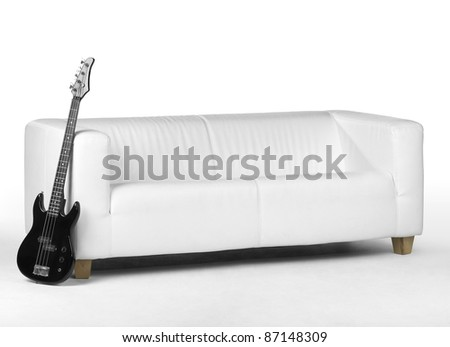 black bass guitar lean against white couch in white back