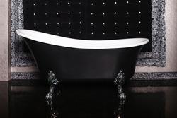 Black bathroom interior with freestanding classic black bathtub on decorative feet. Freestanding bathtub on beautiful silver decorative feet. Elegant bathroom in dark black colors. Royal artsy style