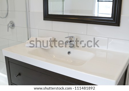 Black bathroom vanity and mirror in a contemporary bathroom