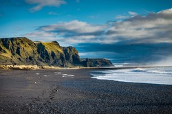 Black Beach and Sea-stacks in Vik Iceland with mountains waves a