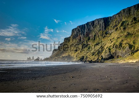 Black Beach and Sea-stacks in Vik Iceland with mountains waves a #750905692