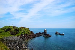 Black beach or cliff from Volcanic rocks with blue sky and ocean at seopjikoji cape, Jeju island, South korea.