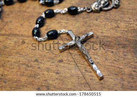 Black beaded rosary on rustic wood background