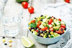 Black beans corn avocado cucumber tomato salad with lime dressing. toning. selective focus