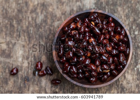 Black beans in wooden bowl. Top view. Copy space