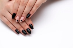 Black, beige matte manicure on long oval nails with painted black hearts on a white background close-up