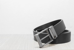 Black belt on wooden table with white background