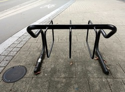 Black bicycle parking rack with water drain cover on the left, side of the bike lane.