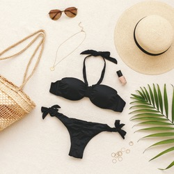 Black bikini swimsuit, straw boater hat, wicker beach bag, sunglasses, gold necklace, rings, tropical palm leave on beige background. Woman's swimwear and beach accessories. Flat lay, top view, outfit