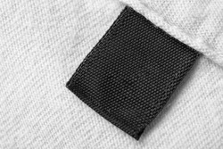Black blank laundry care clothes label on white cotton shirt background
