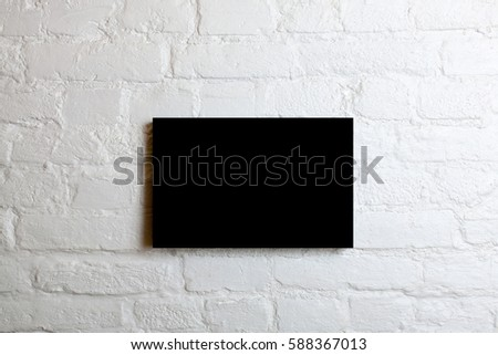 Black blank poster in a white brick wall. Template Mock up for your content. #588367013