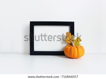 Black blank wooden frame mockup with an orange pumpkin and golden oak leaves lying on the white table. Poster product design. Styled stock feminine photography. Home decor. Autumn, fall concept.
