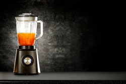 Black blender with juice on a black wall and table background