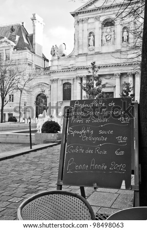 Black board with a menu restaurant in a tipical traditional square in Paris