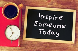 black board with the phrase inspire someone today written on it. over wooden table cup of coffee and vintage clock