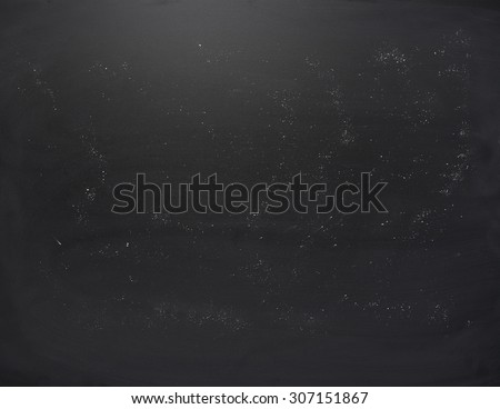 Black board with the traces of chalk over its surface as a background texture