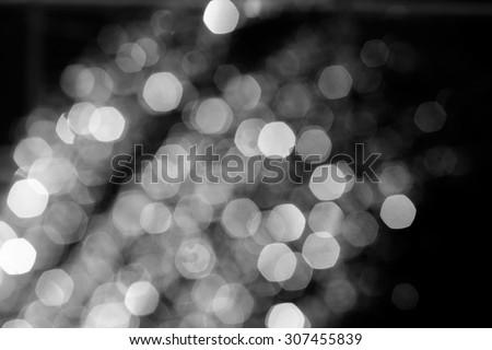 Black bokeh background. Xmas glitter over dark wallpaper. Shiny celebration defocused backdrop.