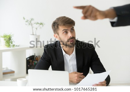 Black boss firing shocked white employee stunned by dismissal notice, confused office worker frustrated by unfair termination looking at executive discharging subordinate with gesture, getting fired
