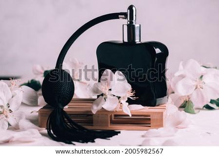 Black bottle eau de toilette or perfume with long tassel spray pomp, on wooden podium in form of pallet on light plaster surface with apple flowers Stock fotó ©