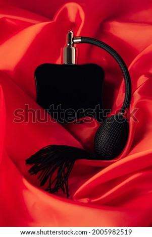Black bottle of eau de toilette or perfume with long tassel spray pomp lies on red background of flowing fabric. Vertical Stock fotó ©