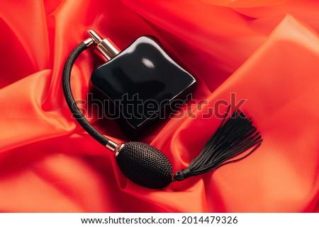 Black bottle of eau de toilette or perfume with long tassel spray pomp lies on red background of flowing fabric Stock fotó ©
