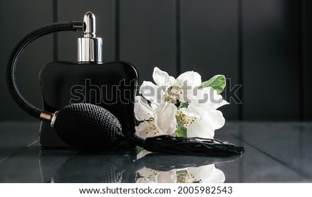 Black bottle of eau de toilette or perfume with long tassel spray pomp stands on dark background on reflective surface with apple blossom. Copy space Stock fotó ©