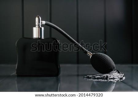 Black bottle of eau de toilette or perfume with long tassel spray pomp stands on dark background on reflective surface. Copy space Stock fotó ©