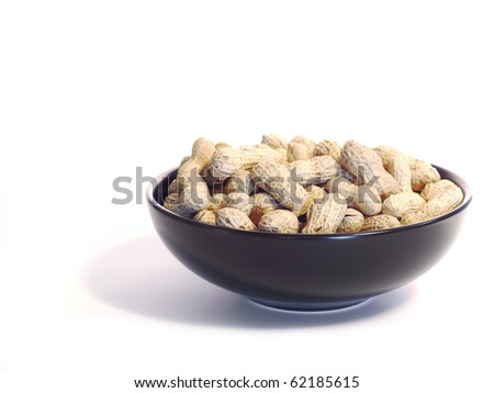 Black bowl with unshelled peanuts, isolated on white.