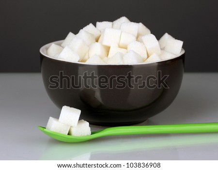 Black bowl with white lump sugar with colorful spoon on grey background close-up