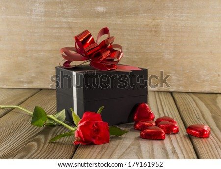 black box present with red rose and heart chocolate shapes