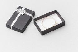 Black box with a silver bracelet, on a grey backdrop